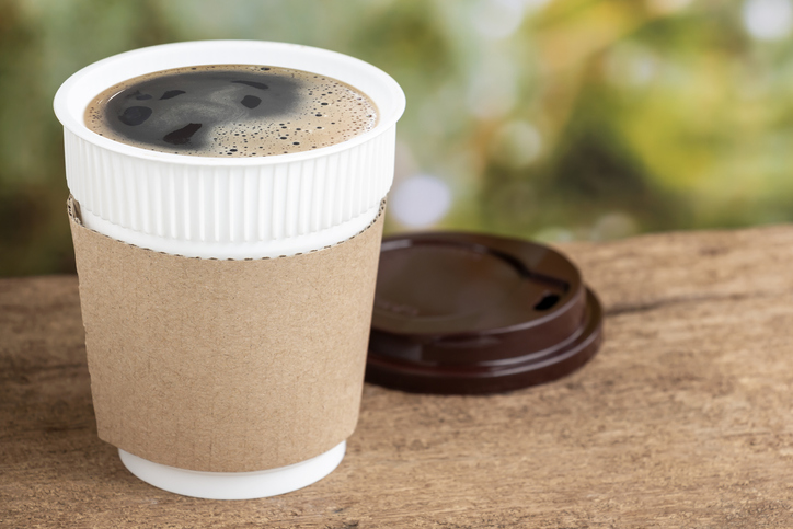 Coffee cup or disposable cup on the wooden table background on natural morning with copy space for your text and logo.